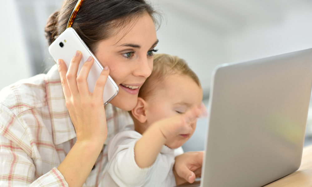 Mother on phone and laptop with baby